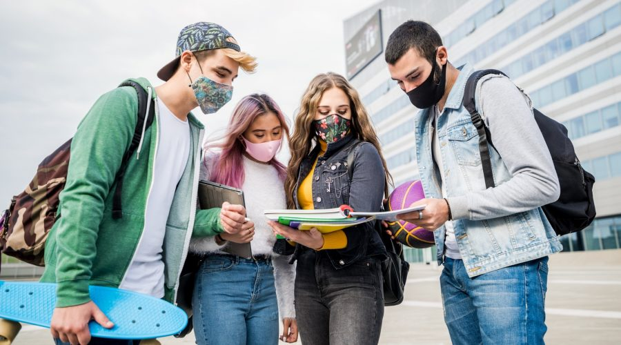 Multiracial students with face mask studying at college campus - New normal lifestyle concept with young students having fun together outdoor.